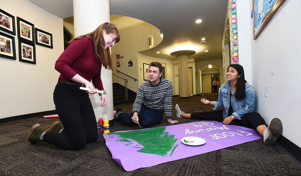 Students working on a banner in residence hall